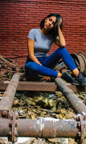 teen posing brick wall